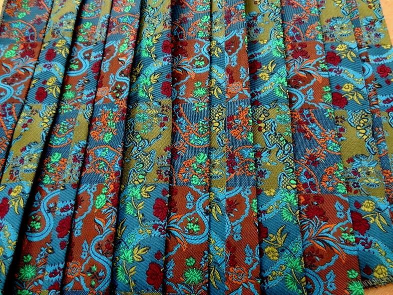 Damas fond bleu canard tissage fleuri plis plats